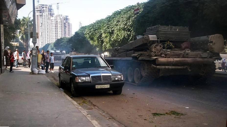 Tanques do regime sírio passam por rua da cidade de Homs