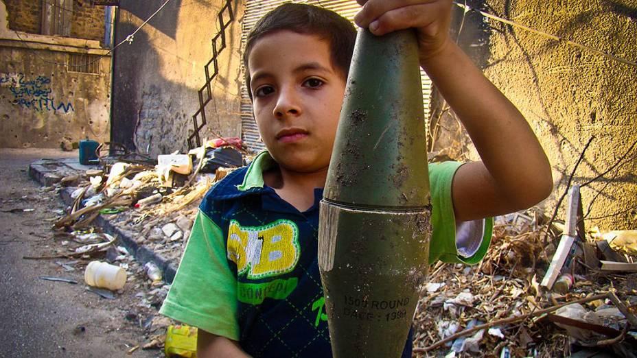 Menino sírio segura morteiro intacto e supostamente disparado por tropas governamentais