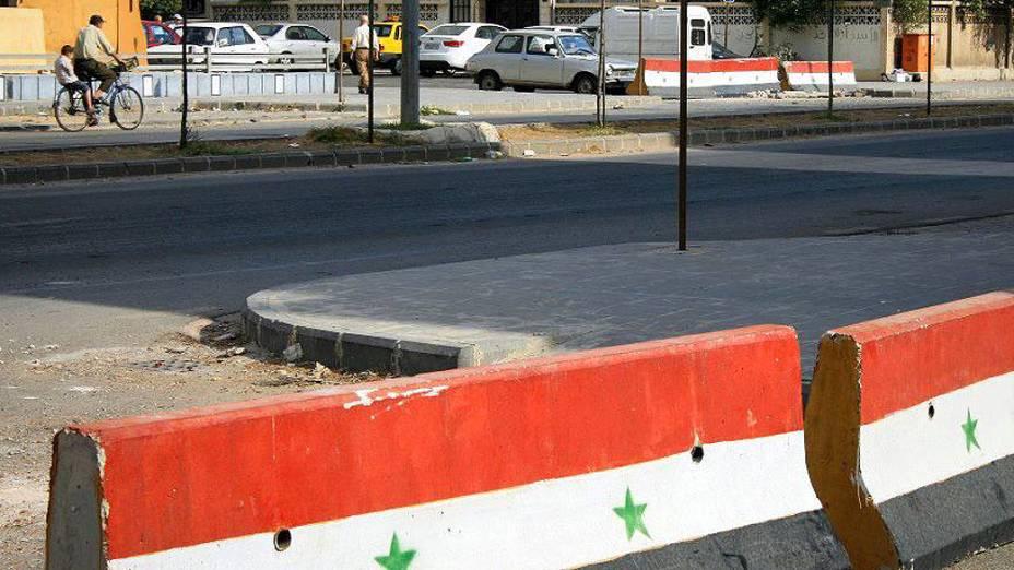 Barreiras de concreto pintados com a bandeira oficial da Síria separam distritos e mostram que estão sob controle de tropas do governo