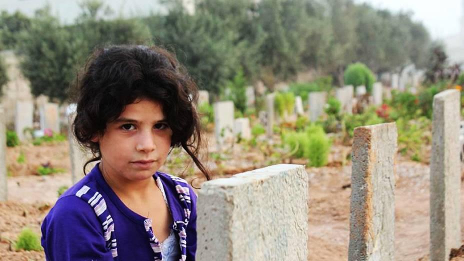 Menina síria em um dos cemitérios da cidade de Homs