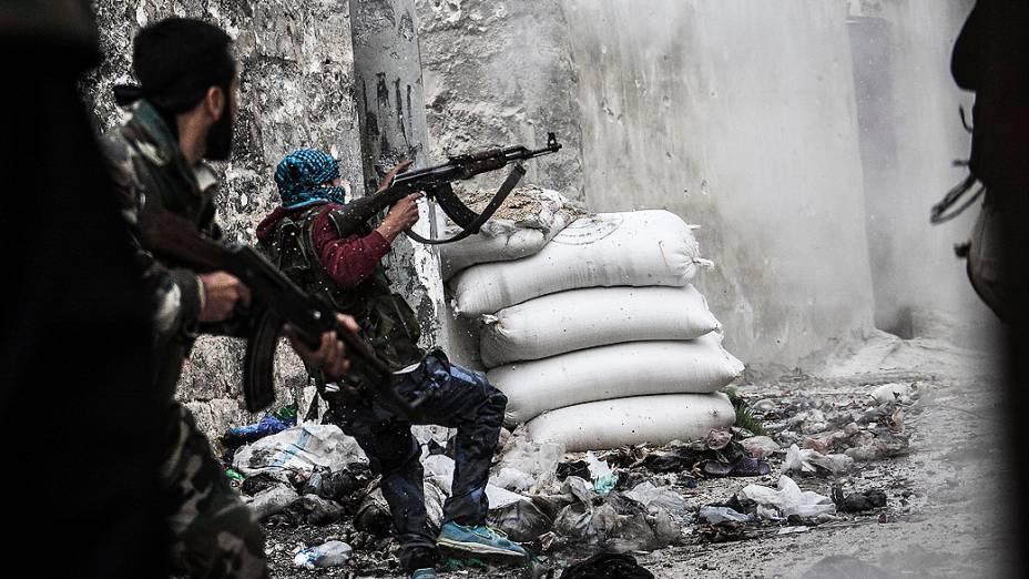 Membro do Exército Livre da Síria em busca de abrigo contra tiros de inimigos na linha de frente de Moaskar, um dos campos de batalha no bairro de Karmal Jabl, em Aleppo