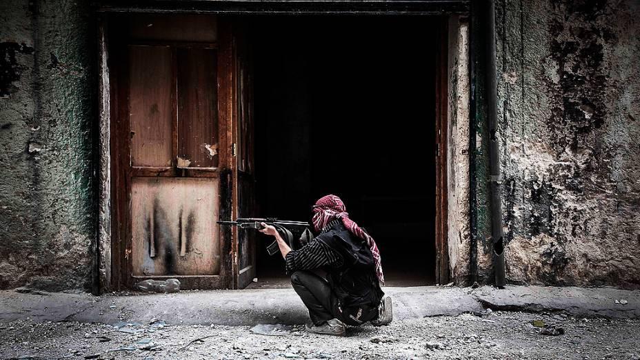 Membro do Exército Livre da Síria dispara contra inimigos na linha de frente de Moaskar, um dos campos de batalha no bairro de Karmal Jabl, em Aleppo