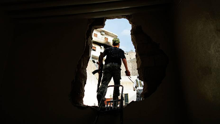 Rebelde é fotografado saido por buraco na parede, na Síria