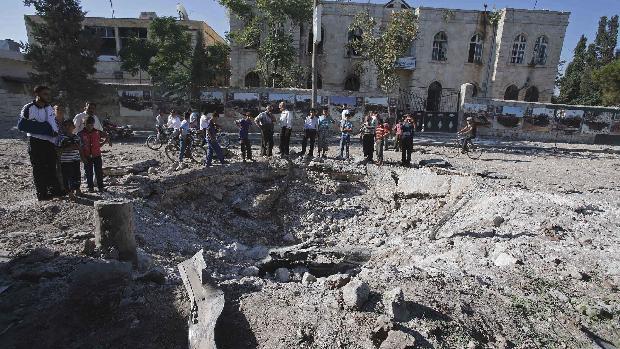 Civis observam destruição causada por bombardeio da força aérea síria na cidade de Azaz