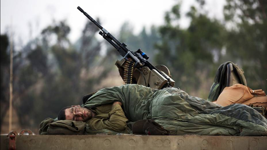 Soldado israelense dorme sobre um tanque-de-guerra próximo a fronteira com a Faixa de Gaza