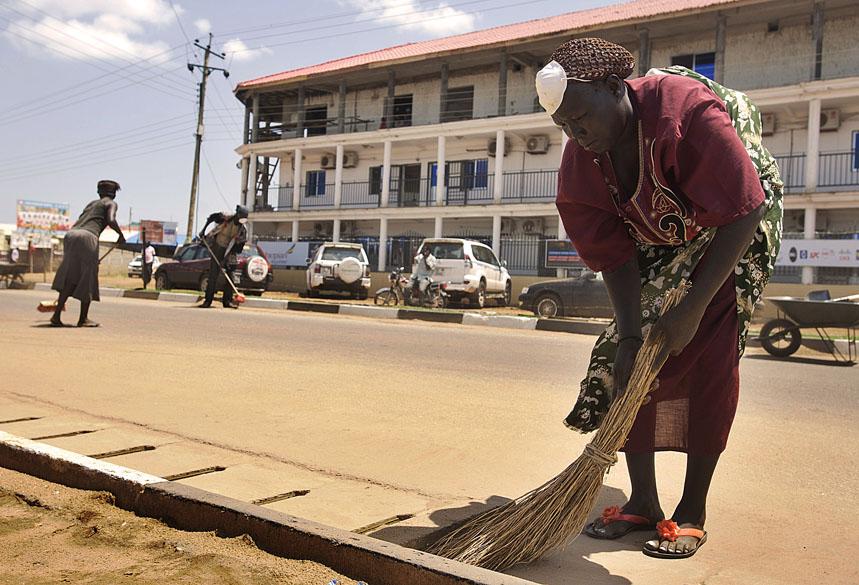 Em Juba, trabalhadora limpa rua para as comemorações do primeiro aniversário do Sudão do Sul