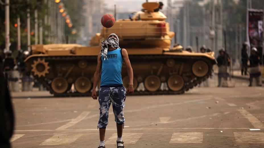 Um apoiador do presidente Mohamed Mursi, joga futebol em frente a tanques do Exército egípcio