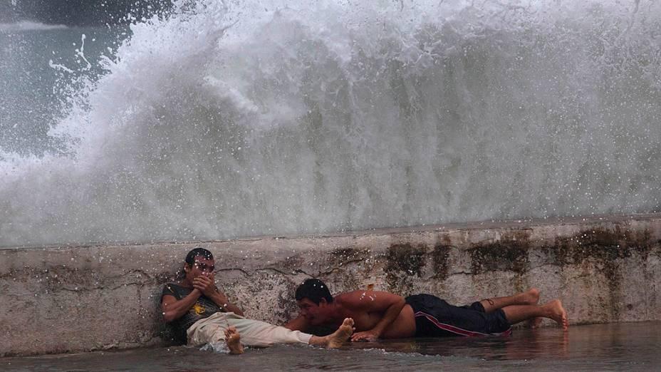 Homens ficam deitados próximo a paredão e observam ondas trazidas pela tempestade tropical Isaac em Baracoa, Cuba