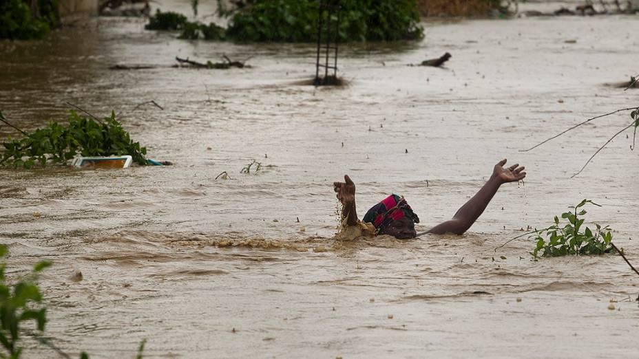 Mulher nada em área inundada pelas chuvas da tempestade tropical Isaac em Porto Príncipe, no Haiti