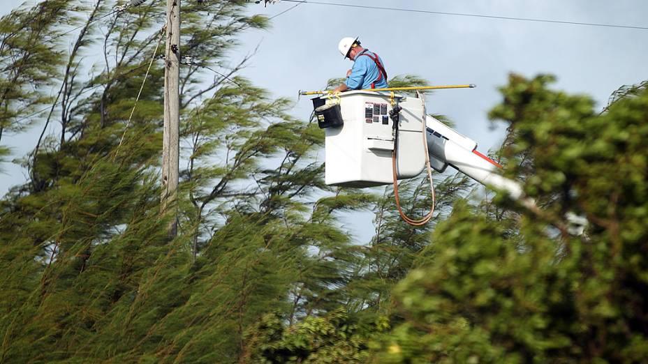 Funcionário da companhia de energia tenta religar os cabos que foram danificados após a passagem da tempestade tropical Isaac, em Key West, cidade da Flória, nos EUA