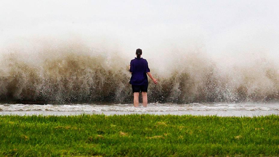 Mulher observa as ondas provocadas pelo vento à beira do lago Pontchartrain em Nova Orleans, com a aproximação do furacão Isaac à cidade