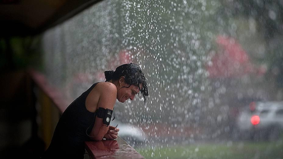Nos Estados Unidos, mulher se refresca na chuva com a aproximação do furacão Isaac