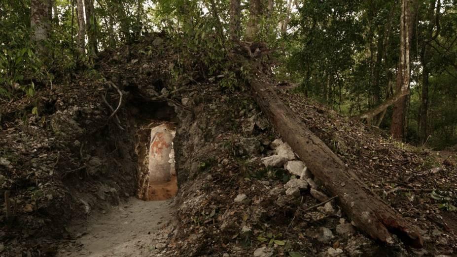 <p>A figura de um homem, possivelmente um escriba que viveu na casa construída pelos maias, é iluminada na porta que dá acesso à residência, no nordeste da Guatemala. É a primeira casa maia encontrada com representações artísticas nas paredes.</p>