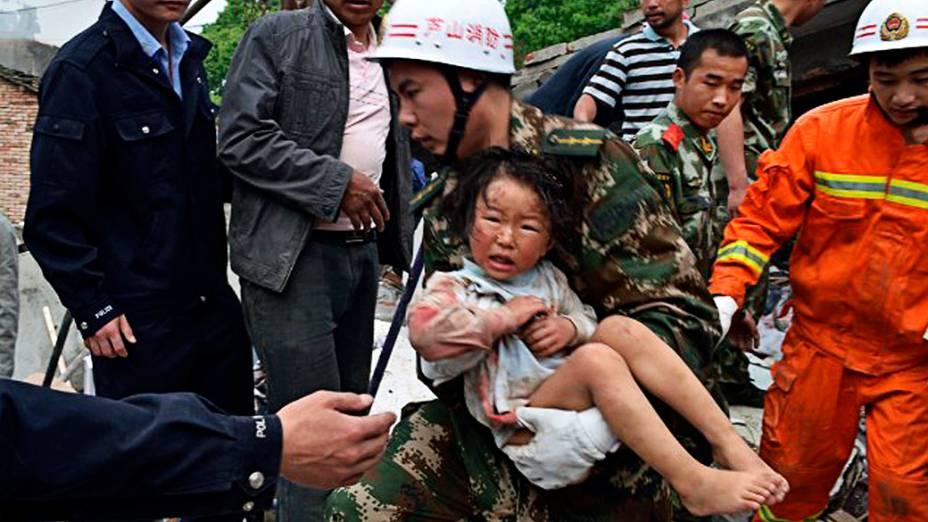 Equipe de resgate socorre criança na província chinesa de Sichuan neste sábado, após terremoto que deixou mais de 150 mortos