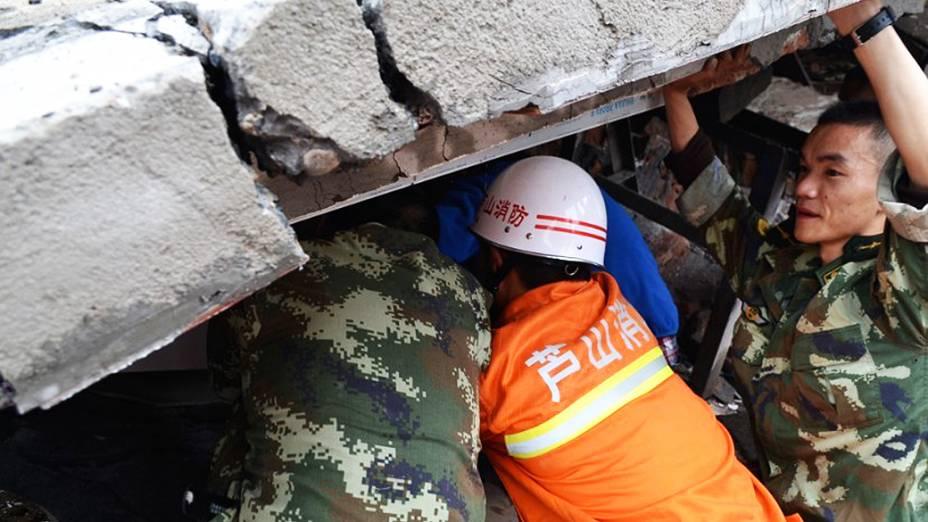 Homens resgatam criança dos destroços após um terremoto ter atingido a província central chinesa de Sichuan neste sábado