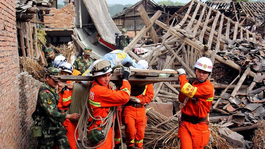 Equipes resgatam idosa na província chinesa de Sichuan, neste domingo (21), após terremoto que deixou mais de 150 mortos