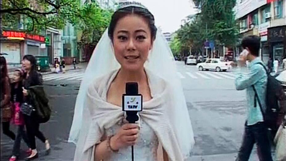 A jornalista Chen Ying grava uma reportagem sobre a tragédia na China usando seu vestido de noiva após terremoto que atingiu a província de Sichuan. A jornalista e noiva fez a reportagem e depois seguiu para o próprio casamento