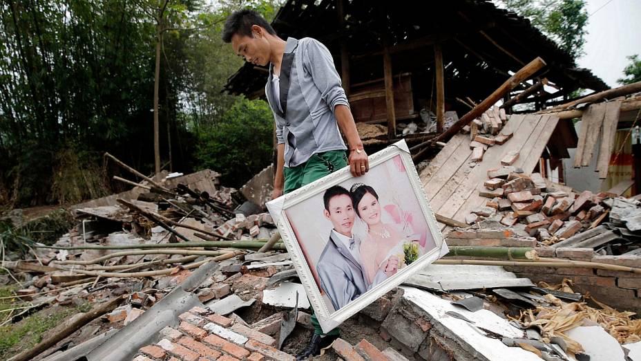 Homem recolhe foto de seu casamento de sua casa, destruída pelo terremoto