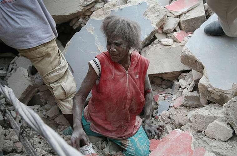Após ficar presa nos escombros, mulher é resgatada.
