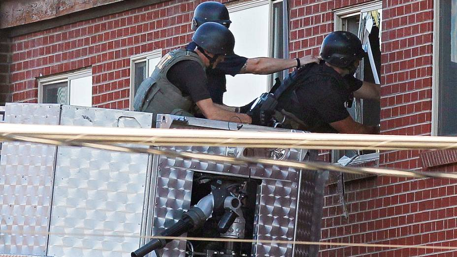 Polícia usa uma câmera de vídeo para investigar apartamento do suspeito de atirar em dezenas de pessoas em cinema no Colorado durante exibição do novo filme do Batman