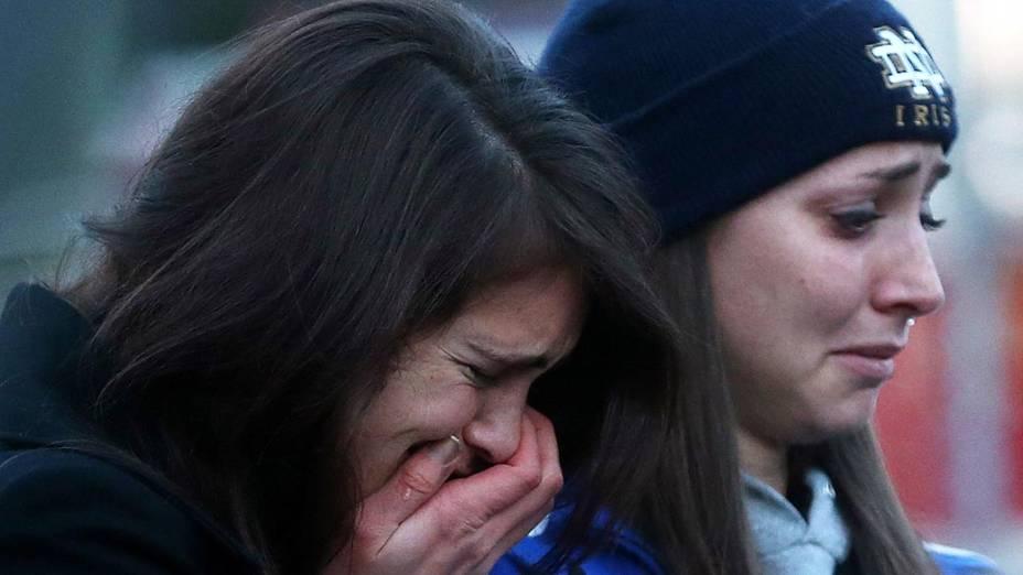 Habitantes da cidade de Newtown na frente da escola primária Sandy Hook, onde 27 pessoas foram mortas na sexta (16/12)