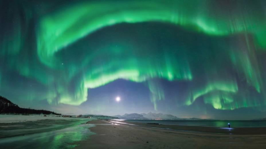 <p>Aurora na praia de Steinsvik, Noruega. O evento não durou mais do que dez minutos, mas iluminou todo o céu e pegou o fotógrafo de surpresa. O homem à direita é seu irmão, procurando seu equipamento para capturar a visão. O autor da imagem conta que foi difícil não rir enquanto movia a câmera para fazer o panorama</p>