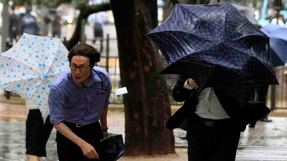 Pedestres se protegem com guarda-chuvas de vento forte e chuva causada pelo tufão Bolaven em Seul