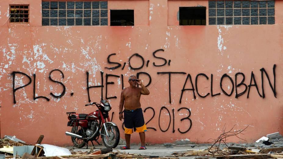 Filipino em frente a frase S.O.S, por favor ajudem Tacloban