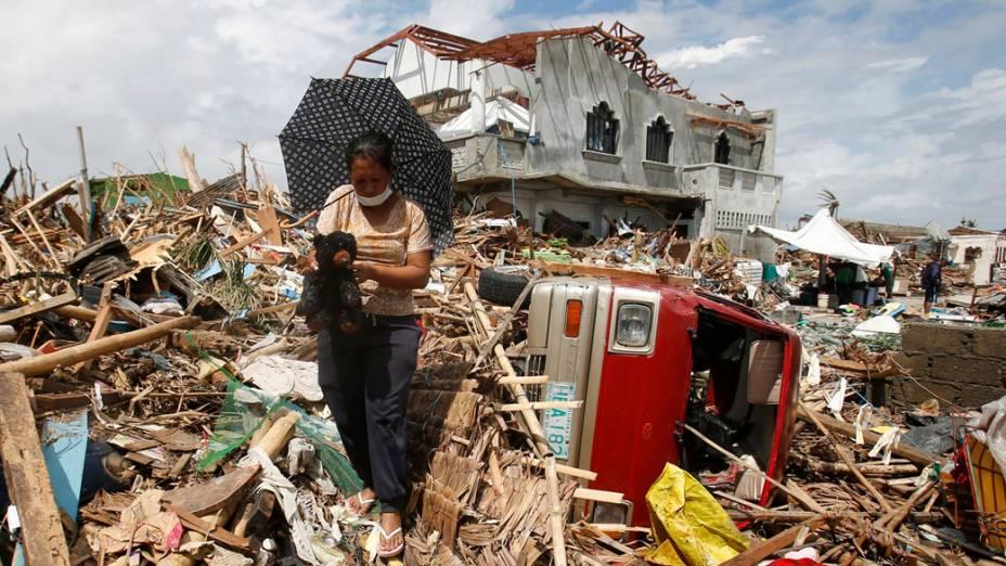 Mulher recupera um ursinho de pelúcia entre os escombros, em Tanauan, nas Filipinas