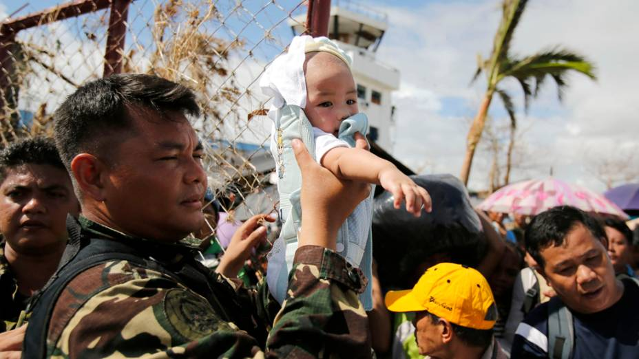 Em Tacloban, soldado segura bebê antes de embarcar para a capital Manila