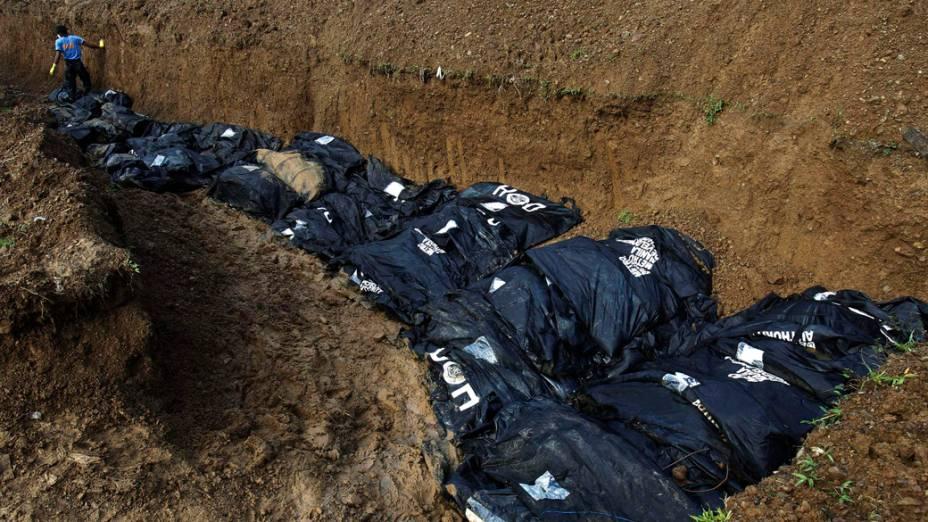 Policial arruma corpos para enterro em uma vala comum, em Tacloban