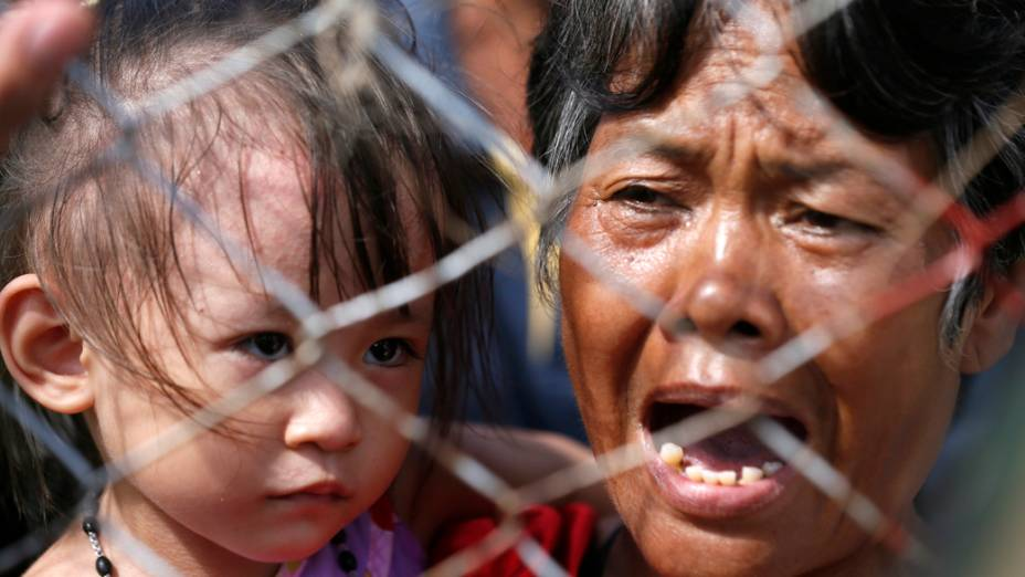 No aeroporto de Tacloban, mulher espera para ser levada de helicóptero para Manila