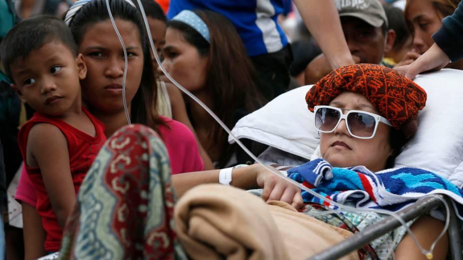 Mulher ferida é socorrida no aeroporto de Tacloban. Milhares de pessoas aguardam para serem transportadas para a capital Manila