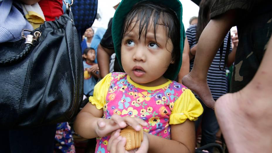 Menina recebe bolachas enquanto espera para embarcar para Manila, nas Filipinas