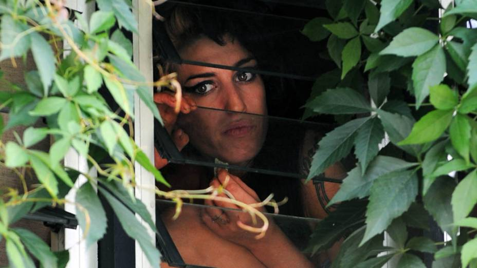 Amy Winehouse na janela de sua casa em Londres em 2008