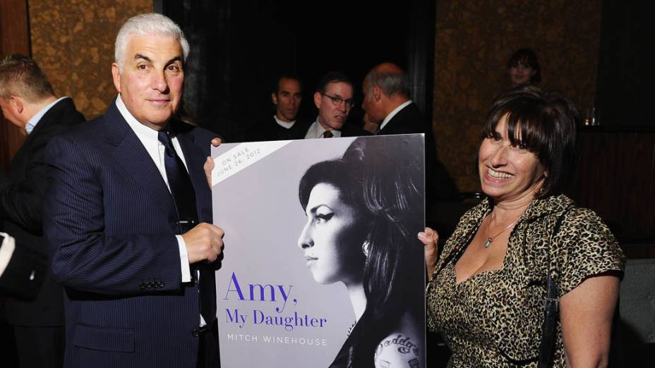 Pais de Amy, Mitch e Janis Winehouse, seguram cartaz com a capa do livro escrito por Mitch