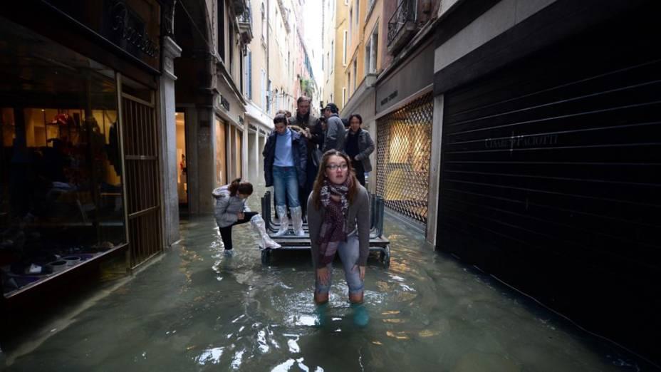 Venezianos e turistas se deslocam pela cidade inundada