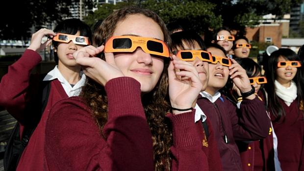 <p>Alunos de um colégio em Sidnei, Austrália, observam o fenômeno com óculos de proteção</p>
