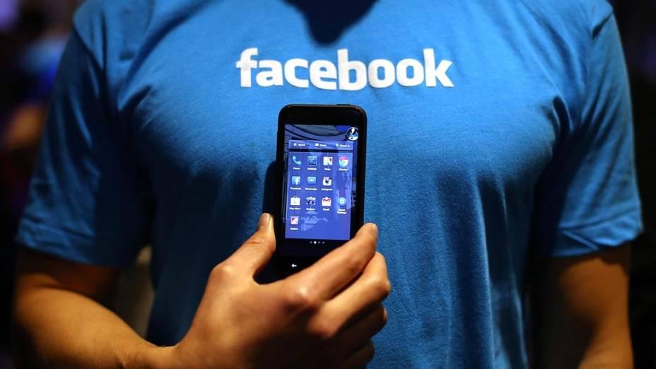Homem segura um celular com o programa do Facebook Home