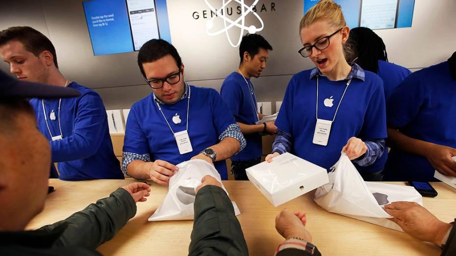 Funcionários atendem clientes durante compras do novo iPad Air dentro Apple Store na Quinta Avenida, em Nova York