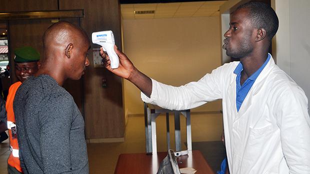 Agente de saúde verifica um passageiro na saídado aeroporto de Conacri, na República da Guiné. As medidas fazem parte de um programa de ações contra a propagação do vírus Ebola em todo o continente africano