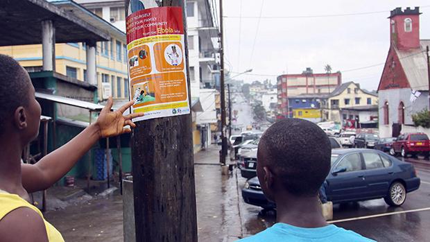 Na Libéria, homensleemum cartaz com informações sobre a prevenção do vírus Ebola, na cidade de Monróvia