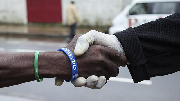 Um homem usa luvas de plástico para evitar contaminação pelovírus Ebola, na cidade deMonrovia, na Libéria