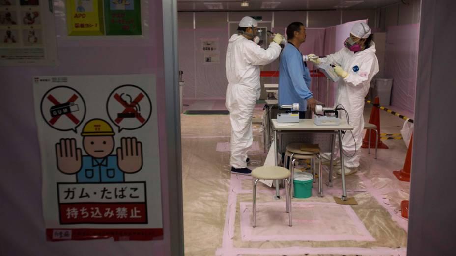 Trabalhador é examinado após entrar no centro de operações de emergência, do complexo nuclear de Fukushima, no Japão
