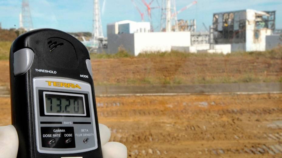Jornalista mostra medidor com o nível de radioatividade nos prédios da usina nuclear de Fukushima, no Japão