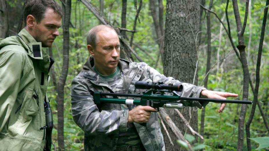 Vladimir Putin com uma arma de tranquilizantes durante visita a Academia de Ciências Ussuri, na Rússia, em agosto de 2008