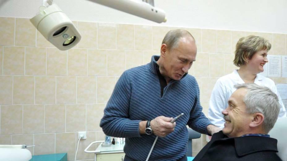 Vladimir Putin brinca com Yevgeny Savchenko, governador de Belgorod, em uma sala de odontologia em novembro de 2011