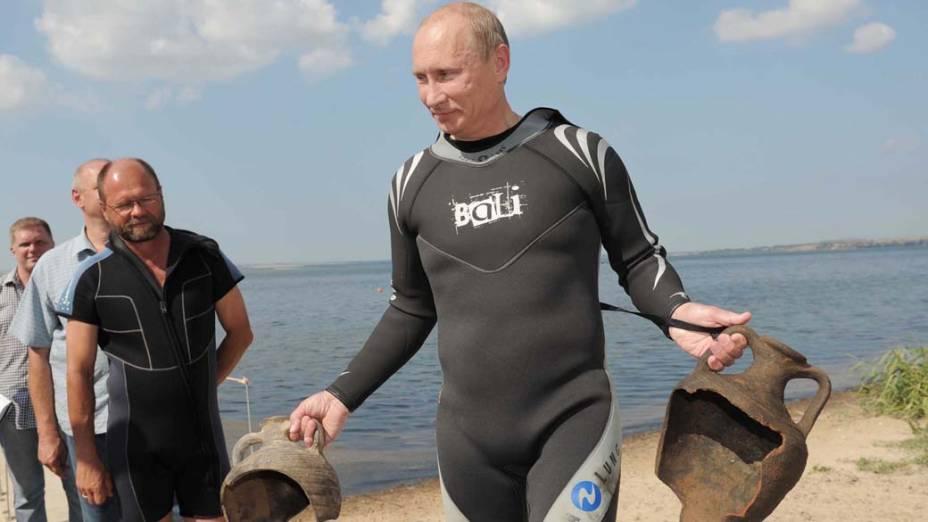 Vladimir Putin carrega duas ânforas que encontrou enquanto mergulhava na Península de Taman na Rússia em agosto de 2011