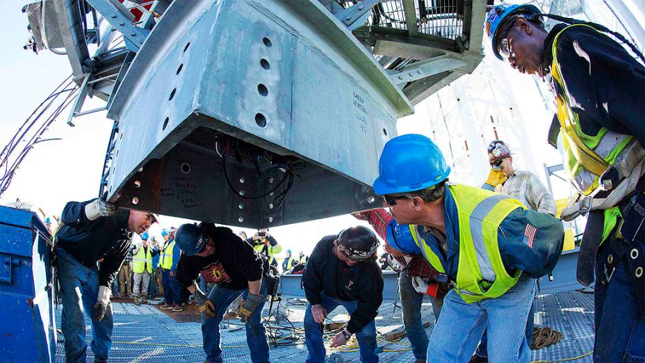 Trabalhadores olham para os nomes assinados dentro da última peça da torre no alto do One World Trade Center em Nova York