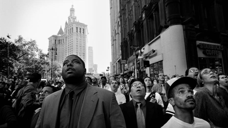 Nova-iorquinos observam o colapso da primeira torre do World Trade Center, no ataque terrorista de 11 de setembro de 2001, em Nova York